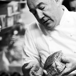 Arnaud Delmontel ajoutant des graines de pavot en décoration sur un cake citron-pavot, artisan boulanger pâtissier à Paris