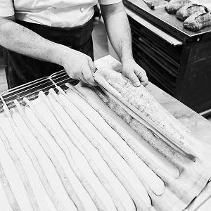 Arnaud Delmontel déposant un pâton de baguette pour la mettre au four, artisan boulanger pâtissier à Paris