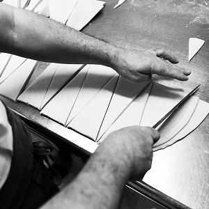 Arnaud Delmontel découpe des triangles dans la pâte feuilletée pour rouler les croissants, artisan boulanger pâtissier à Paris